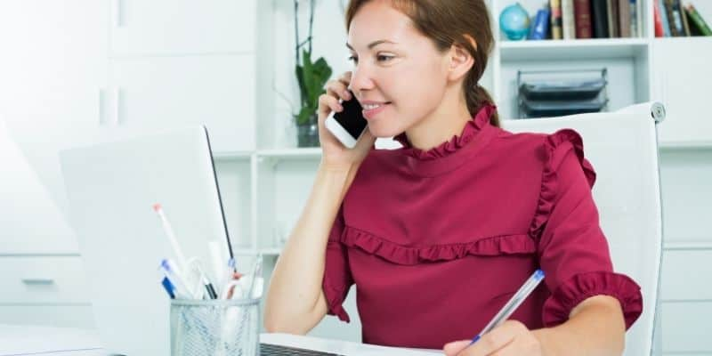 virtual assistant working on laptop while talking on phone