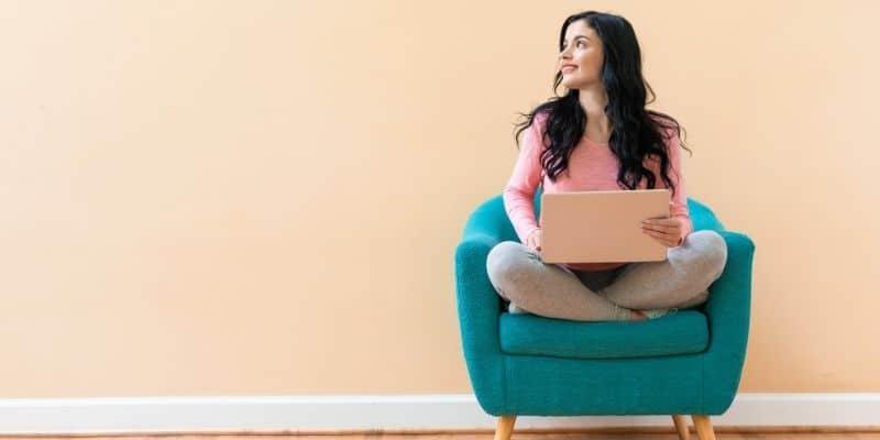 woman sitting cross legged on chair holding laptop