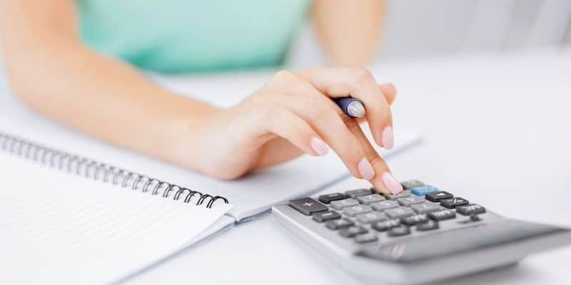 Woman bookkeeping with calculator, pen and notebook.