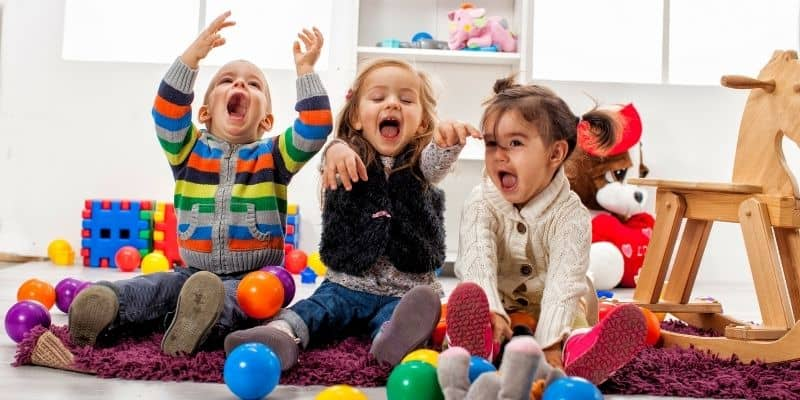 3 young children in daycare surrounded by toys
