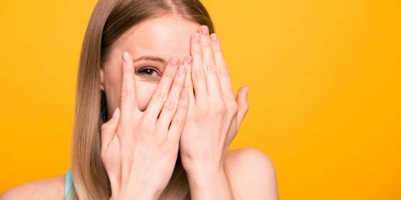 woman hiding face behind hands