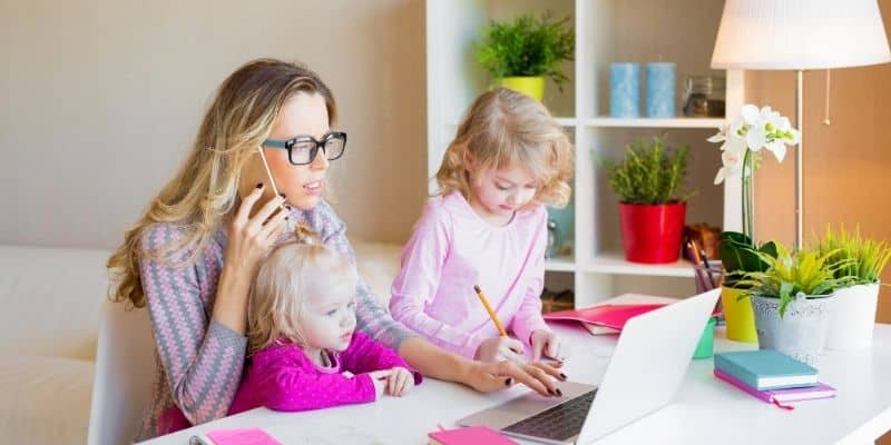 Mom working on laptop, sitting with two children