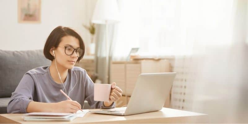 woman transcribing with cup of coffee, using laptop and earbuds.