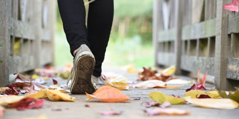 feet walking on coloured autumn leaves