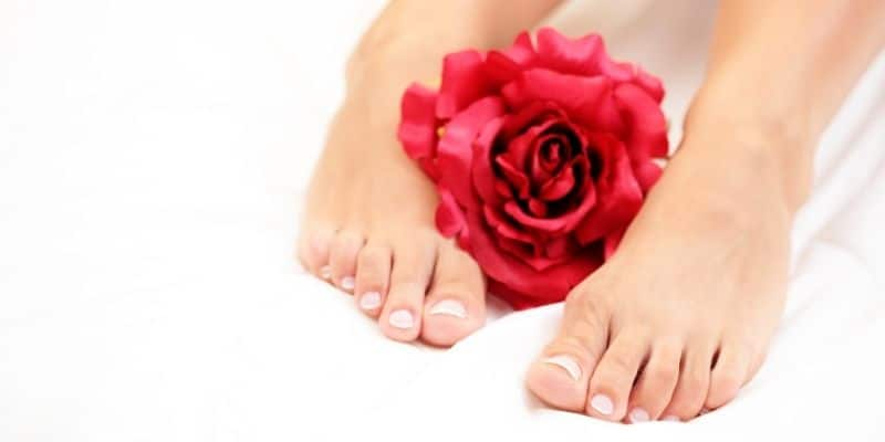 Example feet pic - 2 bare feet with natural painted nails either side of red rose