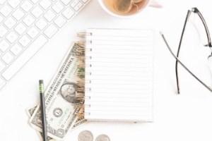 dollar bills tucked under bank notepad beside brewing tea and keyboard