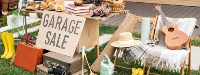 Garage sale sign surround by items such as books, suitcases, guitar and clothing