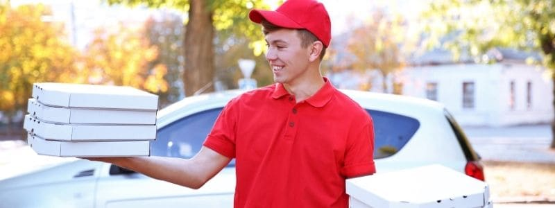 Young male pizza delivery driver standing in front of car holding pizza boxes